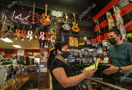 Customer Hermalinda Marquez talks with Jose Antonio Olvera, 49, owner of Olvera Music on Whittier Blvd. in East Los Angeles, while picking up an alto sax belonging to her daughter that was brought in for repair. The area has been hit hard as the economy begins to reopen. (Mel Melcon / Los Angeles Times)