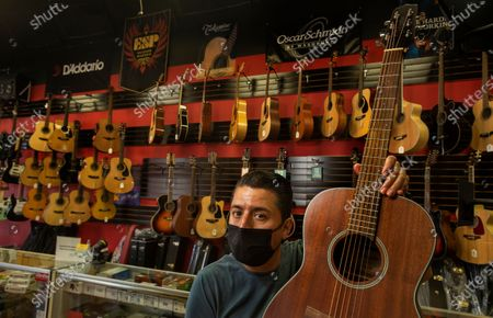 Jose Antonio Olvera, 49, owner of Olvera Music on Whittier Blvd. in East Los Angeles, is photographed inside his store on April 7, 2021. The area has been hit hard as the economy begins to reopen. (Mel Melcon / Los Angeles Times)
