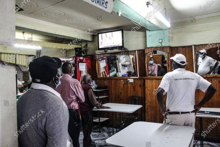 People are seen watching a live broadcast of President Uhuru Kenyatta at a café in Nakuru Town. Recent Covid-19 restrictions reduced gatherings as a preventive measure against a new wave of infections, so to hotels only serving take-away food it has led to increased job losses and decreased revenues in hotels across the country.