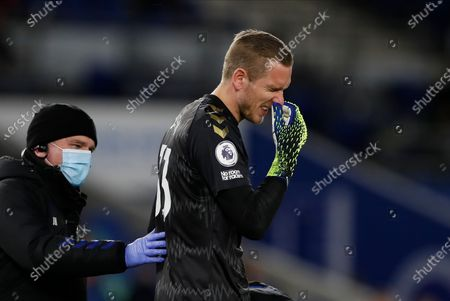 Everton's goalkeeper Robin Olsen receives medical care after a clash during the English Premier League match between Brighton & Hove Albion and Everton in Brighton, Britain, 12 April 2021.