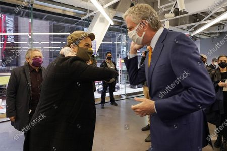Actor Lin-Manuel Miranda, center, and New York Mayor Bill de Blasio, bump elbows before they tour the grand opening of a Broadway COVID-19 vaccination site intended to jump-start the city's entertainment industry, in New York, . At left is Miranda's father. Luis A. Miranda, Jr