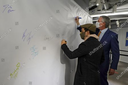 Actor Lin-Manuel Miranda, left, and New York Mayor Bill de Blasio, sign the autograph wall after they toured the grand opening of a Broadway COVID-19 vaccination site intended to jump-start the city's entertainment industry, in New York