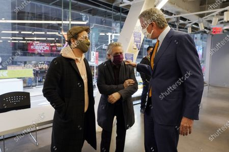 Actor Lin-Manuel Miranda, left, and his father, Luis A. Miranda, Jr., center, talk with New York Mayor Bill de Blasio, before they tour the grand opening of a Broadway COVID-19 vaccination site intended to jump-start the city's entertainment industry, in New York