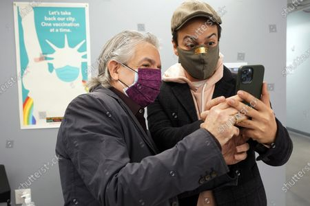 Actor Lin-Manuel Miranda, right, and his father, Luis A. Miranda, Jr., look at a mobile phone before they tour the grand opening of a Broadway COVID-19 vaccination site intended to jump-start the city's entertainment industry, in New York