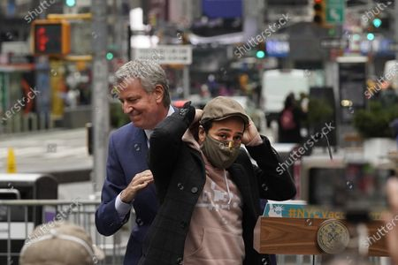 Actor Lin-Manuel Miranda, right, and New York Mayor Bill de Blasio, pass each other at the podium before Miranda's remarks in Times Square, after they toured the grand opening of a Broadway COVID-19 vaccination site intended to jump-start the city's entertainment industry, in New York