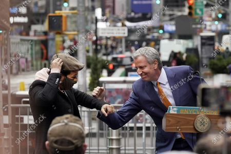 Stock Photo of Actor Lin-Manuel Miranda, left, and New York Mayor Bill de Blasio, bump elbows in Times Square after they toured the grand opening of a Broadway COVID-19 vaccination site intended to jump-start the city's entertainment industry, in New York