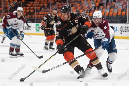 Anaheim Ducks center Ryan Getzlaf, center, controls the puck away from Colorado Avalanche defenseman Cale Makar in an NHL hockey game in Anaheim, Calif