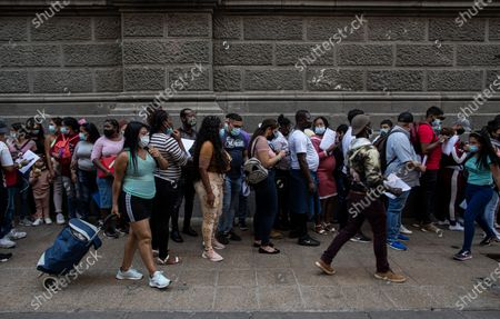 Stock Picture of People seeking to regularize their immigration status line up to receive help to fill out a form at a migrant organization at the Plaza de Armas despite a lockdown to contain the spread of COVID-19, in Santiago, Chile, . Chilean President Sebastian Pinera enacted a new immigration law on Sunday that will facilitate administrative expulsions of immigrants