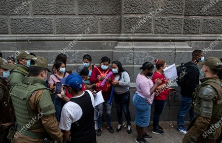 Police check papers as people seeking to regularize their immigration status line up to receive help to fill out a form at a migrant organization at the Plaza de Armas despite a lockdown to contain the spread of COVID-19, in Santiago, Chile, . Chilean President Sebastian Pinera enacted a new immigration law on Sunday that will facilitate administrative expulsions of immigrants