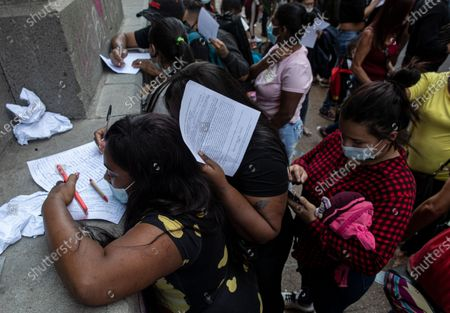 Stock Photo of People fill out forms seeking to regularize their immigration status, near a Church at the Plaza de Armas during a lockdown to contain the spread of COVID-19, Santiago, Chile, . Chilean President Sebastian Pinera enacted a new immigration law on Sunday that will facilitate administrative expulsions of immigrants