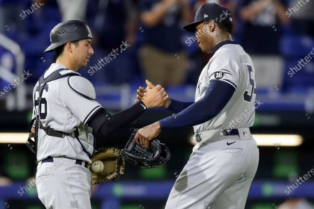 New York Yankees catcher Kyle Higashioka, left, celebrates with Aroldis Chapman at the end of a win over the Toronto Blue Jays in a baseball game, in Dunedin, Fla