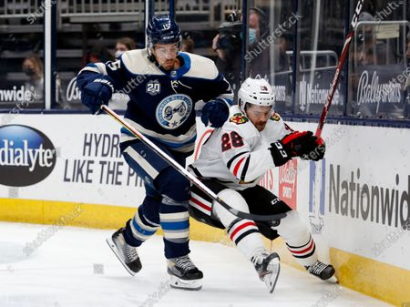 Columbus Blue Jackets defenseman Michael Del Zotto, left, checks Chicago Blackhawks forward Vinnie Hinostroza during the first period of an NHL hockey game in Columbus, Ohio