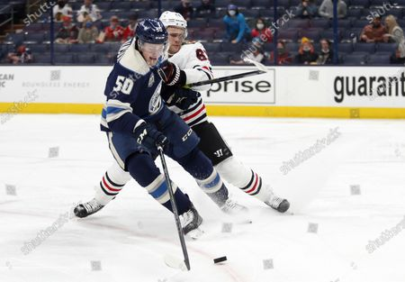 Columbus Blue Jackets forward Eric Robinson, left, tries to control the puck against Chicago Blackhawks defenseman Riley Stillman during the second period of an NHL hockey game in Columbus, Ohio
