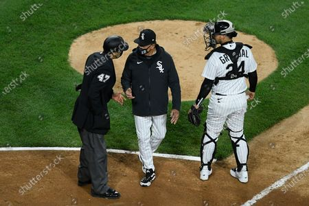Chicago White Sox manager Tony La Russa, center, argues with home plate umpire Gabe Morales (47) while catcher Yasmani Grandal (24) looks on during the ninth inning of a baseball against the Cleveland Indians, in Chicago. Chicago won 4-3
