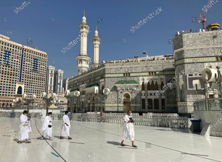 Muslim pilgrims walk outside the Grand Mosque, during the minor pilgrimage, known as Umrah, marking the holy month of Ramadan, in the Muslim holy city of Mecca, Saudi Arabia, . During Ramadan, the holiest month in Islamic calendar, Muslims refrain from eating, drinking, smoking and sex from dawn to dusk