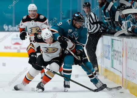 Anaheim Ducks left wing Andrew Agozzino (26) battles for the puck against San Jose Sharks left wing Evander Kane (9) during the first period of an NHL hockey game, in San Jose, Calif