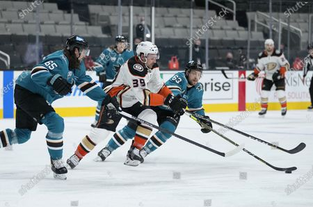 Anaheim Ducks center Sam Carrick (39) moves the puck up the ice past San Jose Sharks' Erik Karlsson (65) and Jeffrey Truchon-Viel (63) during the second period of an NHL hockey game, in San Jose, Calif