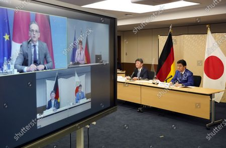 Japan's Foreign Minister Toshimitsu Motegi (2-R) and Defence Minister Nobuo Kishi (R) attend a video conference with German Foreign Minister Heiko Maas (top L, on screen) and Defence Minister Annegret Kramp-Karrenbauer (top R, on screen) at the Foreign Ministry in Tokyo, Japan, 13 April 2021. The two countries held Foreign and Defense Ministerial Meeting, '2+2', to strengthen their cooperation.