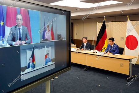 """Japanese Foreign Minister Toshimitsu Motegi, second from right, and Defense Minister Nobuo Kishi, right, attend a video conference with German Foreign Minister Heiko Maas, top left on screen, and German Defense Minister Annegret Kramp-Karrenbauer, top right on screen, at Foreign Ministry in Tokyo during their """"2 plus 2"""" ministerial meeting"""