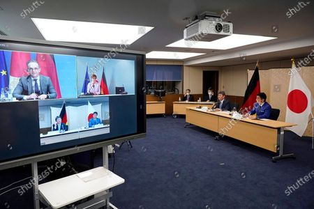 """Japanese Foreign Minister Toshimitsu Motegi, second from right, and Japanese Defense Minister Nobuo Kishi, right, attend a video conference with German Foreign Minister Heiko Maas, top left on screen, and German Defense Minister Annegret Kramp-Karrenbauer, top right on screen, at Foreign Ministry in Tokyo during their """"2 plus 2"""" ministerial meeting"""