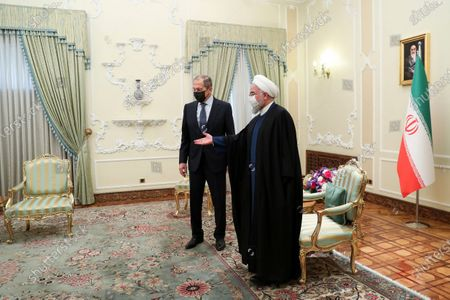 In this photo released by the official website of the office of the Iranian Presidency, Iranian President Hassan Rouhani, right, welcomes Russian Foreign Minister Sergey Lavrov, for their meeting in Tehran, Iran