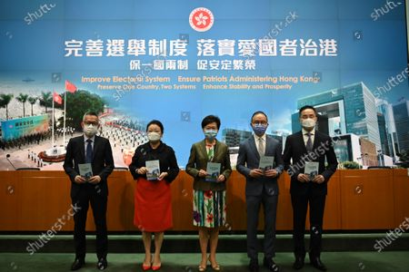 Stock Picture of From Left to Right Ms Llewellyn Mui, Acting Officer(Special Duties), Ms Teresa Cheng, Secretary for Justice, Mrs Carrie Lam, Chief Executive of Hong Kong, Mr Eric Tsang, Secretary for constitution and mainland affairs, Mr Roy Tang, permanent secretary for Constitutional and Mainland affairs hols up booklet during a press conference on 'Improving Electoral System' in Hong Kong, China, on April 13, 2021. The government is formally proposing to make it a crime for people to urge others to cast blank or spoiled ballots, or not vote at all, as it unveiled a host of bills to amend local laws in line with the sweeping electoral reforms initiated by Beijing last month. It would also be a crime to obstruct or prevent people from casting a ballot. Both offences would be punishable by up to three years in prison, The paper also laid out detailed arrangements for how the expanded 1,500-member Election Committee will be selected in an election to be held on September 19, The powerful body will nominate all legislators and select 40 of them through block-voting, That means each member selects 40 members, and the 40 individuals with the most votes at the end will win the seats, All members will be required to swear allegiance to the SAR, and vow to uphold the Basic Law, The Election Committee would also keep its current role of choosing the chief executive, with the next election set for March 27, Authorities also unveiled the 10 new geographical constituencies that will return 20 of the 90 new legislators to be chosen on December 19. The paper also laid out detailed arrangements for how the expanded 1,500-member Election Committee will be selected in an election to be held on September 19.