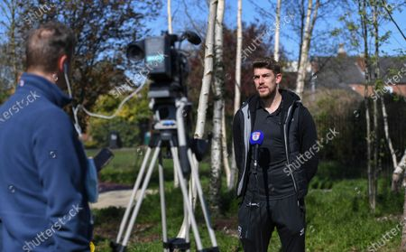 Alex Palmer of Lincoln City gives a TV interview on the EFL Day of Action as he helps members of the Sincil Community Land Trust create a garden near Lincoln City's home stadium