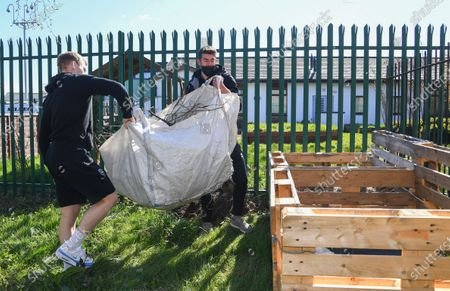 Alex Palmer and Anthony Scully of Lincoln City help members of the Sincil Community Land Trust create a garden near Lincoln City's home stadium during the EFL Day of Action
