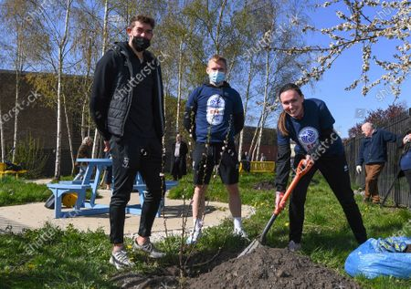 Alex Palmer and Anthony Scully of Lincoln City with Alice Carter who works on Lincoln City's community projects plant a tree as they help members of the Sincil Community Land Trust create a garden near Lincoln City's home stadium during the EFL Day of Action