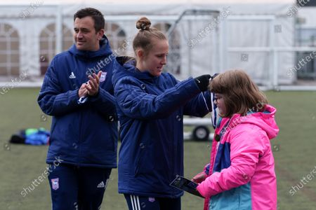 Local school children take part in the EFL Day of Action at Portman Road as Ipswich Town Women's Eva Hubbard hands out a participation medal