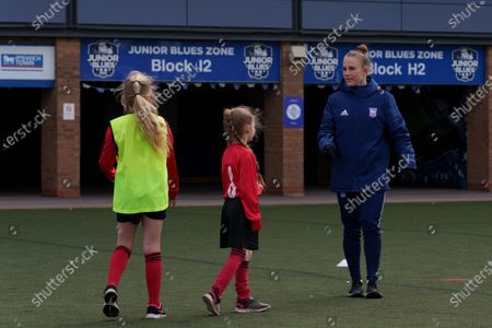 Stock Image of Ipswich Town Women's Eva Hubbard works with local school children during the EFL Day of Action / Girls Football Festival at Portman Road.