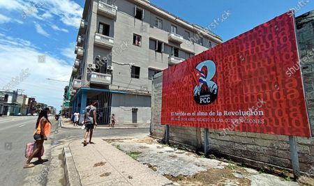 People walk in front of a banner that promotes the VIII Congress of the Communist Party of Cuba (PCC), to be held from 16 April to 19 April in Havana, Cuba, 13 April 2021. The generational change with the withdrawal of Raul Castro, the serious economic crisis and the loss of the hegemony of discourse due to the irruption of the internet are some of the challenges that the Cuban communists will face at this summit.