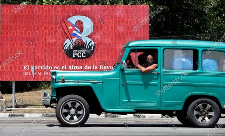 People pass on a vehicle in front of a banner that promotes the VIII Congress of the Communist Party of Cuba (PCC), to be held from 16 April to 19 April in Havana, Cuba, 13 April 2021. The generational change with the withdrawal of Raul Castro, the serious economic crisis and the loss of the hegemony of discourse due to the irruption of the internet are some of the challenges that the Cuban communists will face at this summit.