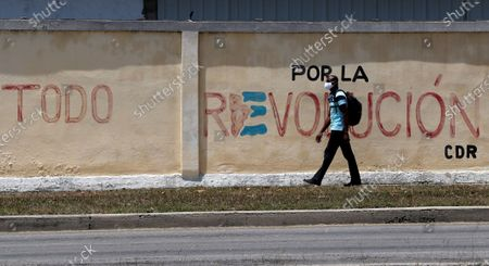 A man walks in front of a mural in support of the Cuban Revolution, days before the VIII Congress of the Communist Party of Cuba (PCC), to be held from 16 April to 19 April in Havana, Cuba, 13 April 2021. The generational change with the withdrawal of Raul Castro, the serious economic crisis and the loss of the hegemony of discourse due to the irruption of the internet are some of the challenges that the Cuban communists will face at this summit.