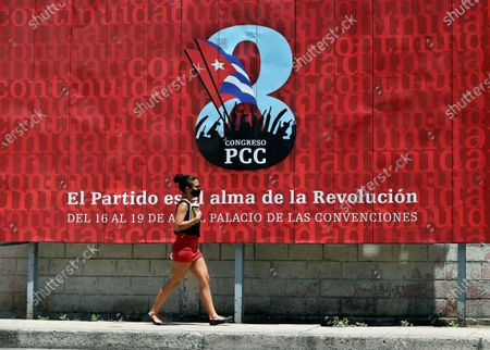 A woman walks in front of a banner that promotes the VIII Congress of the Communist Party of Cuba (PCC), to be held from 16 April to 19 April in Havana, Cuba, 13 April 2021. The generational change with the withdrawal of Raul Castro, the serious economic crisis and the loss of the hegemony of discourse due to the irruption of the internet are some of the challenges that the Cuban communists will face at this summit.