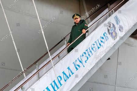 In this handout photo released by Russian Defense Ministry Press Service, Russian Defense Minister Sergei Shoigu steps down from the Admiral Kuznetsov aircraft carrier while visiting a naval base in in Gadzhiyevo, Russia, . Shoigu on Tuesday described a massive military buildup in western Russia as part of drills intended to check the armed forces' readiness amid the threats posed by NATO