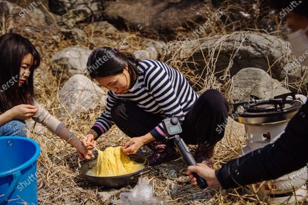 Sim Ha Yoon, from left, Seok Hyeon Ju, and Kim Mi Ran document their afternoon together preparing food and picnicking by a river in Inje, South Korea, Monday March 9, 2020. Seok Hyeon Ju is part of a burgeoning niche of YouTubers N North Korean refugees telling their own stories of escape, survival and resettling in a capitalist land. What had been a couple dozen North Korean YouTubers has surged to more than 150 during the COVID-19 pandemic, when opportunities for speeches, performances and lectures for the refugees has dried up. Many of them young, tech-savvy and attractive, they are changing the image South Koreans have of the 33,000-some North Korean escapees now living among them. (Marcus Yam / Los Angeles Times)