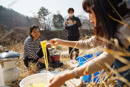 Stock Photo of Seok Hyeon Ju, from left, Kim Mi Ran and Sim Ha Yoon, document their afternoon together preparing food and picnicking by a river in Inje, South Korea, Monday March 9, 2020. Seok Hyeon Ju is part of a burgeoning niche of YouTubers N North Korean refugees telling their own stories of escape, survival and resettling in a capitalist land. What had been a couple dozen North Korean YouTubers has surged to more than 150 during the COVID-19 pandemic, when opportunities for speeches, performances and lectures for the refugees has dried up. Many of them young, tech-savvy and attractive, they are changing the image South Koreans have of the 33,000-some North Korean escapees now living among them. (Marcus Yam / Los Angeles Times)