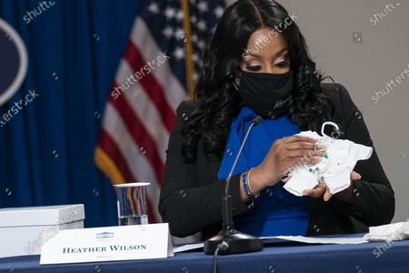 Heather Wilson, Executive Director and Founder of Kennedy's Angel Gowns, holds clothing for deceased babies during a roundtable discussion on Black maternal health hosted by Vice President Kamala Harris and White House Domestic Policy Advisor Susan Rice in the South Court Auditorium
