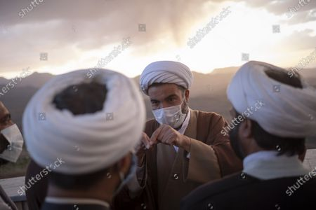 Clerics speak with each other during a ceremony for observation of the new moon of Muslim's holy month of Ramadan in the Imam Ali observatory in Kahak area near the holy city of Qom 145Km (90 miles) south of Tehran at sunset, amid the COVID-19 outbreak in Iran, April 13, 2021.