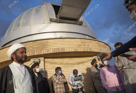 An Iranian man looks at the sky through the binoculars during a ceremony for observation of the new moon of Muslim's holy month of Ramadan in the Imam Ali observatory in Kahak area near the holy city of Qom 145Km (90 miles) south of Tehran at sunset, amid the COVID-19 outbreak in Iran, April 13, 2021.