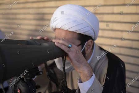 An Iranian cleric looks at the sky through the binoculars during a ceremony for observation of the new moon of Muslim's holy month of Ramadan in the Imam Ali observatory in Kahak area near the holy city of Qom 145Km (90 miles) south of Tehran at sunset, amid the COVID-19 outbreak in Iran, April 13, 2021.