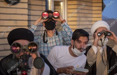 Iranian clerics and astronomers wearing protective face masks look at the sky through the binoculars during a ceremony for observation of the new moon of Muslim's holy month of Ramadan in the Imam Ali observatory in Kahak area near the holy city of Qom 145Km (90 miles) south of Tehran at sunset, amid the COVID-19 outbreak in Iran, April 13, 2021.