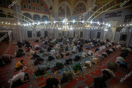 Stock Picture of Worshipers pray as they mark the beginning of Ramadan at the Nizamiye Mosque in Johannesburg, South Africa, 13 April 2021. Muslims around the world celebrate the holy month of Ramadan by praying during the night time and abstaining from eating, drinking, and sexual acts during the period between sunrise and sunset. Ramadan is the ninth month in the Islamic calendar and it is believed that the revelation of the first verse in Koran was during its last 10 nights. The mosque is a copy of the 'Blue Mosque' in Istanbul and was build by a Turkish businessman Ali Katircioglu. The mosque claims to be the biggest in the southern hemisphere.