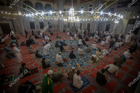 Stock Photo of Worshipers pray as they mark the beginning of Ramadan at the Nizamiye Mosque in Johannesburg, South Africa, 13 April 2021. Muslims around the world celebrate the holy month of Ramadan by praying during the night time and abstaining from eating, drinking, and sexual acts during the period between sunrise and sunset. Ramadan is the ninth month in the Islamic calendar and it is believed that the revelation of the first verse in Koran was during its last 10 nights. The mosque is a copy of the 'Blue Mosque' in Istanbul and was build by a Turkish businessman Ali Katircioglu. The mosque claims to be the biggest in the southern hemisphere.