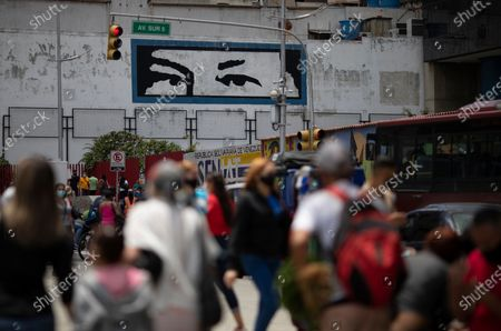"""Mural depicts """"Chavez's eyes,"""" a design based on the eyes of the late Venezuelan President Hugo Chavez, as pedestrians wearing masks to curb the spread of COVID-19, walk in downtown Caracas, Venezuela"""