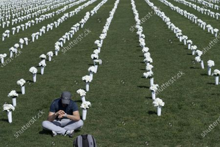 """A man sits among 40,000 white silk flowers on the National Mall displayed to honor those who have died from gun violence as part of an event organized by """"Giffords: Courage to Fight Gun Violence"""" in Washington, D.C., U.S., on Tuesday, April 13, 2021. The advocacy group is lead by Former Congresswoman Gabrielle Giffords who was shot in 2011.      Photo by Sarah Silbiger/UPI"""