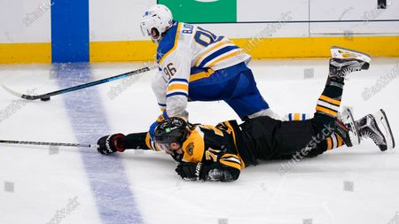 Boston Bruins left wing Taylor Hall (71) dives to try to knock the puck away from Buffalo Sabres forward Anders Bjork, top, during the third period of an NHL hockey game, in Boston