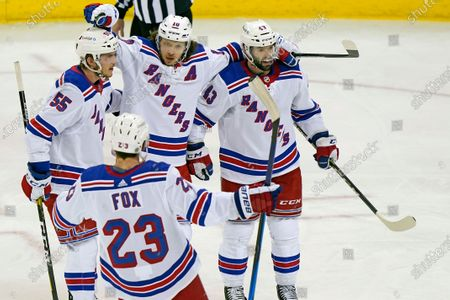New York Rangers left wing Artemi Panarin (10) celebrates with defensemen Adam Fox (23), Ryan Lindgren (55) and center Colin Blackwell (43) after scoring the third period of an NHL hockey game against the New Jersey Devils, in Newark, N.J
