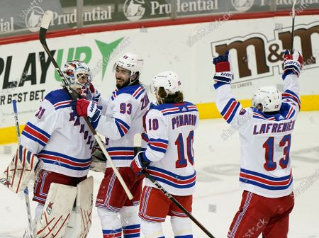From left, New York Rangers goaltender Igor Shesterkin (31), center Mika Zibanejad (93), and left wings Artemi Panarin (10) and Alexis Lafrenière (13) celebrate after the Rangers shut out the New Jersey Devils 3-0 in an NHL hockey game, in Newark, N.J